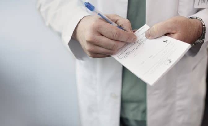 Close up of a male doctor filling out a medical prescription